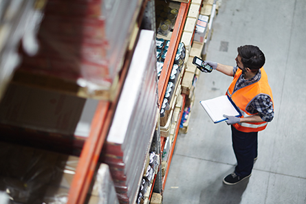 Worker with scanner making review of goods in warehouse